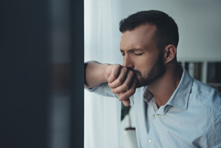 anxiety man up against window eyes closed