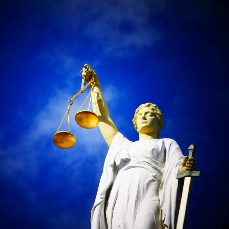 lady justice holding scales in front of blue sky court of appeals for veterans claims