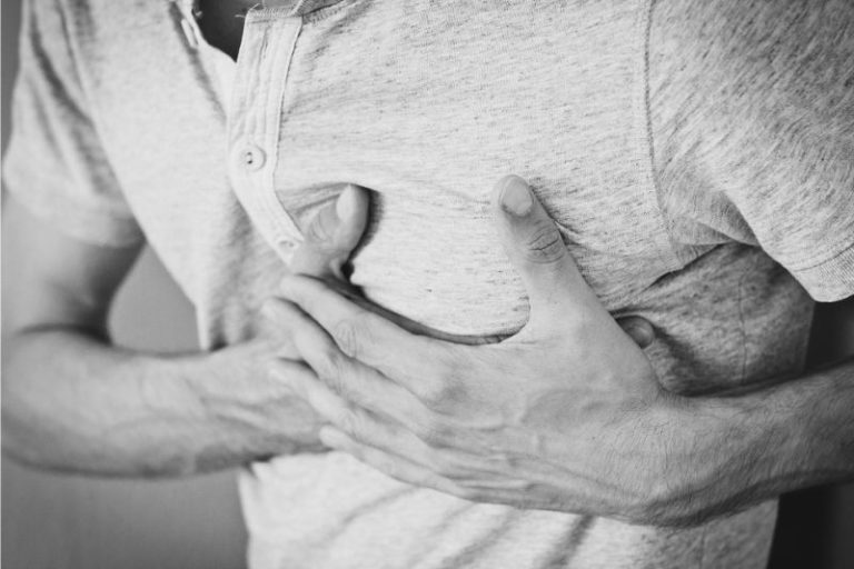 man grabbing chest due to heart condition