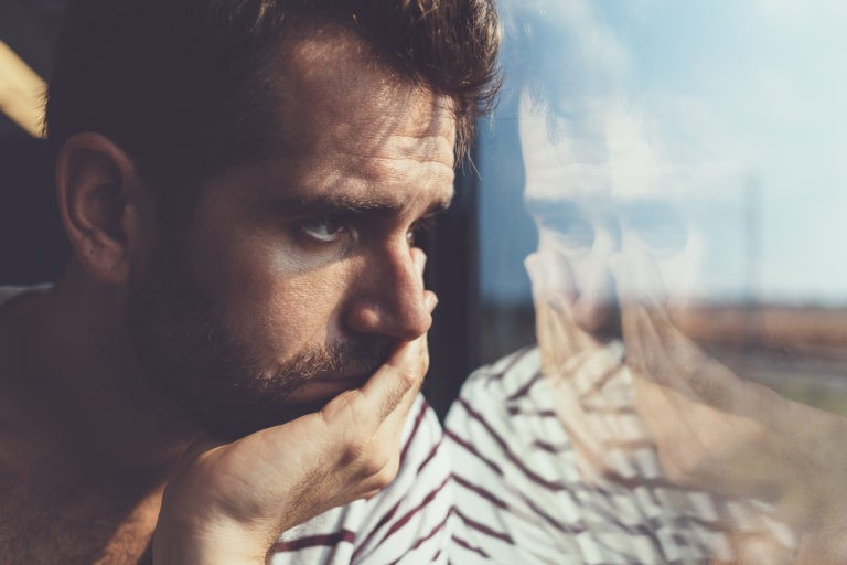 man looking out of window sad struggling with adjustment disorder