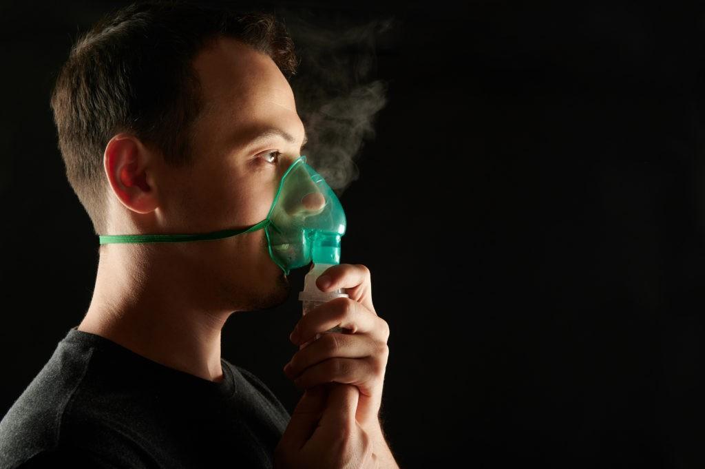 profile of man using nebulizer to treat asthma or sleep apnea