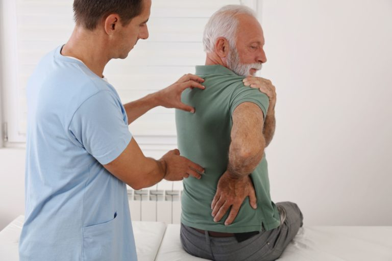 old man being examined by practitioner due to arthritis of the back