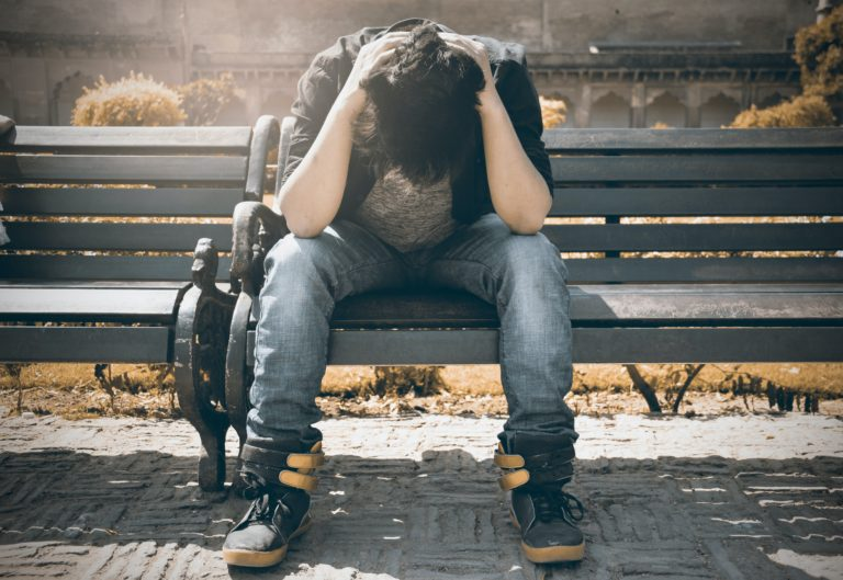 man covering face on city bench due to adjustment disorder with anxiety