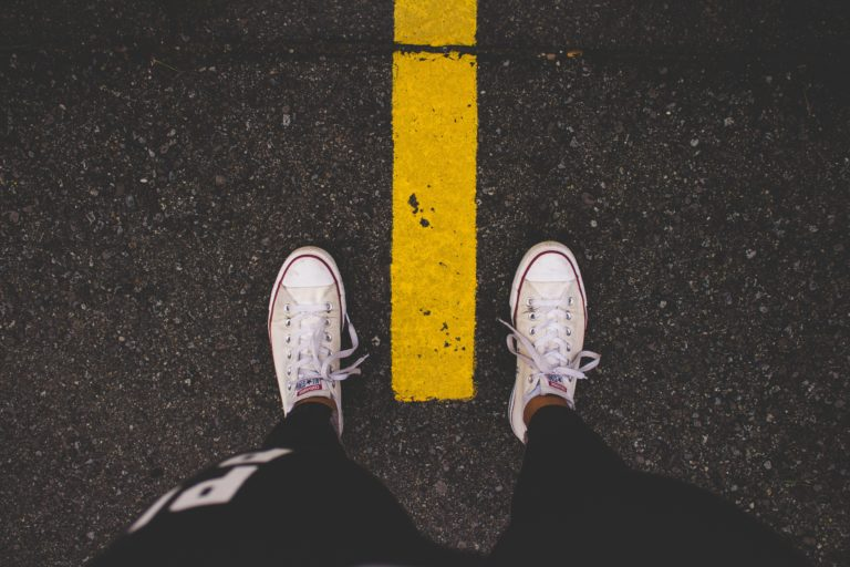 flat feet in white shoes standing on yellow lined paved road