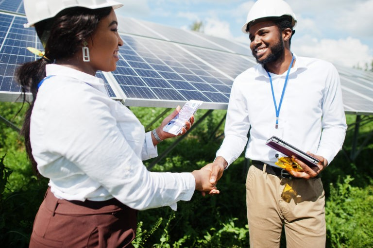 man and woman engineer shaking hands in front of solar panels