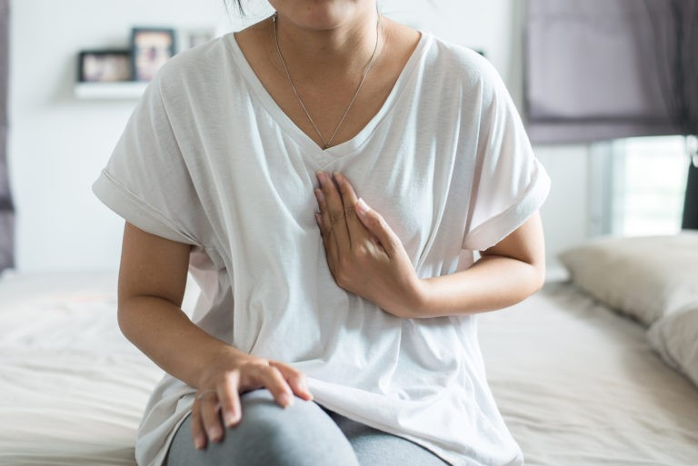 woman in white shirt in white bedroom clutching chest due to acid reflux