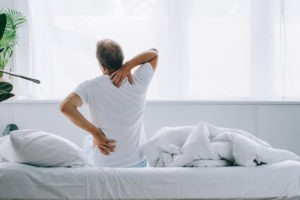 man in all white room stretching in the morning due to pain associated with Intervertebral Disc Syndrome IVDS
