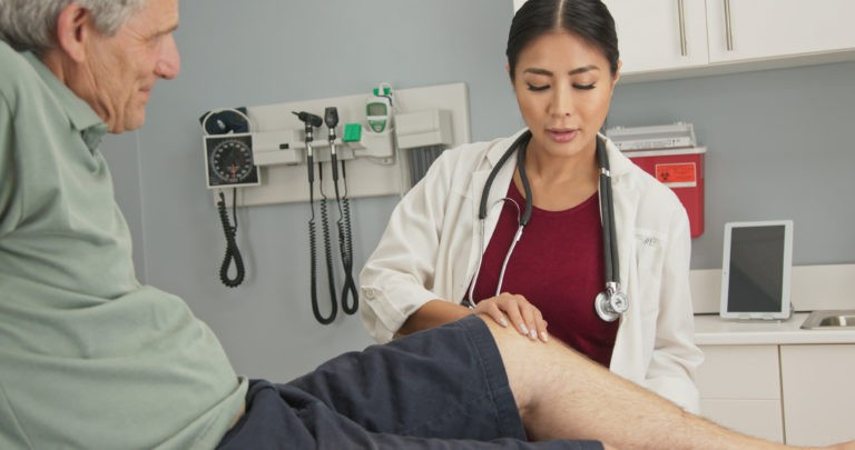 physical therapist measuring older man's knee range of motion due to Torn Meniscus