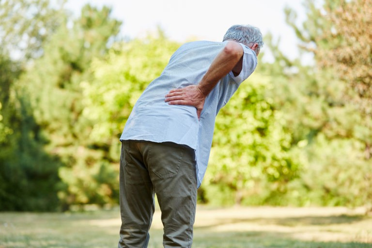 old man in green field suffering from back pain due to limited range of motion