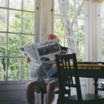 man over 65 sitting in kitchen with sprawling windows reading Good Life newspaper