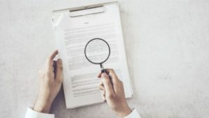 doctor reviewing claim letter with magnifying glass